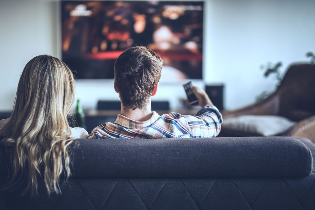 Rear view of a couple watching TV while relaxing on the sofa at home.
