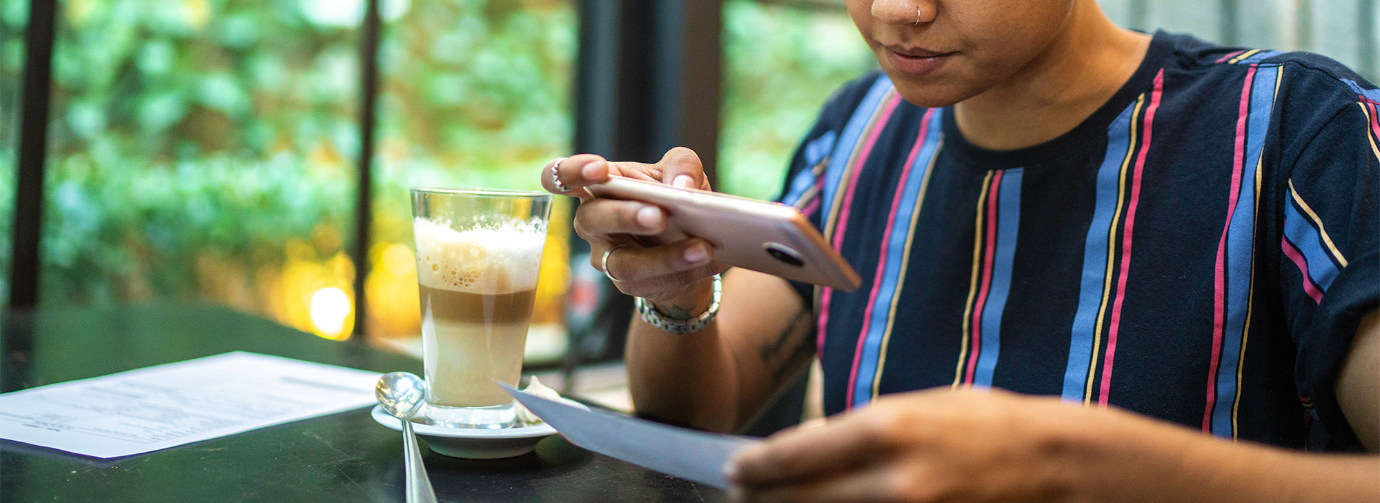 woman in cafe using mobile remote deposit financial banking
