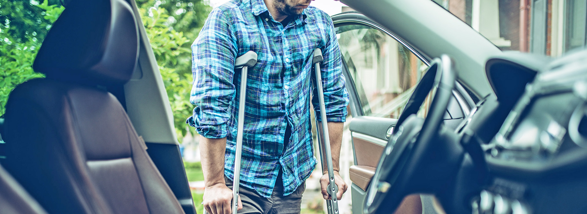 man using crutches to get into car. image represents home, auto, health and life insurance all in one.