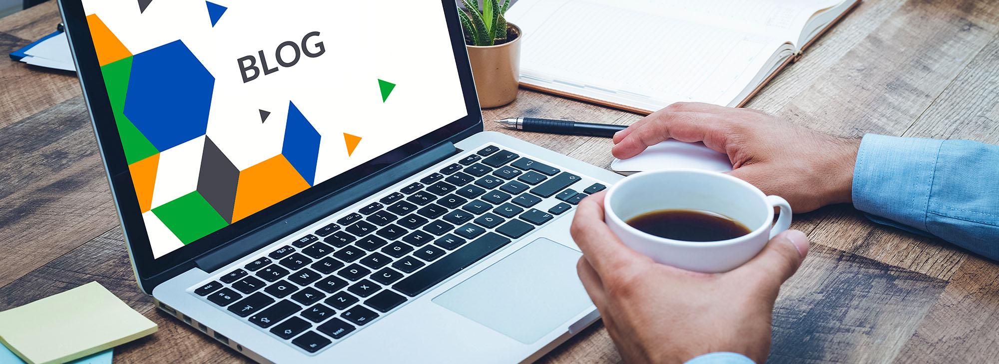 man at work reading blog on laptop while drinking coffee