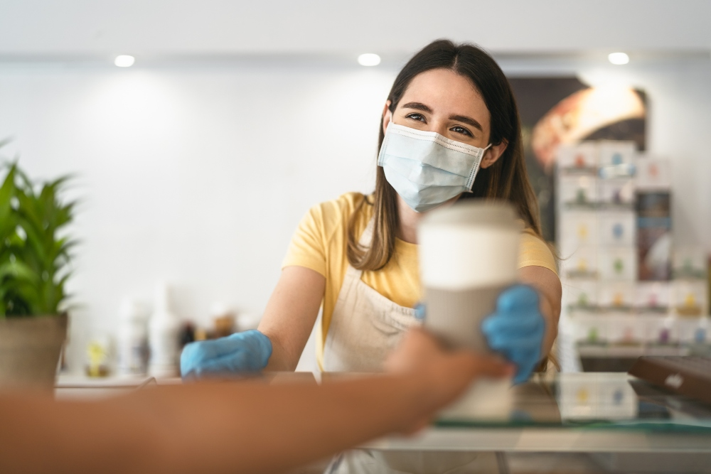 female barista handing coffee to a customer while wearing a mask