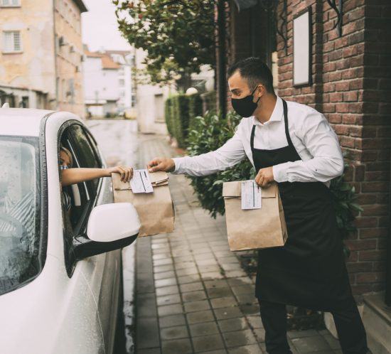 Male c-store employee delivers a curbside pickup order to a female driver outside